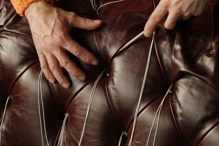 hand-stitching a leather sofa, the producers of which have signed a design manifesto