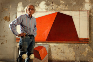 Artist Christo in front of a painting of an orange pyramid