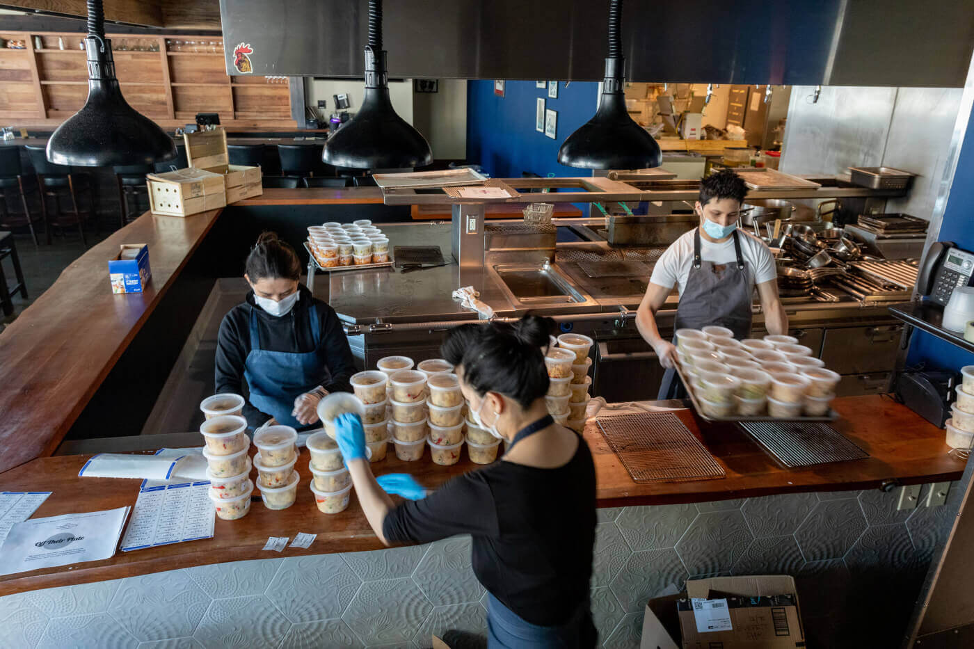 Employees at a restaurant preparing meals for pandemic frontline workers