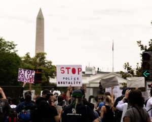 protesters marching against racial injustice with washington monument in background