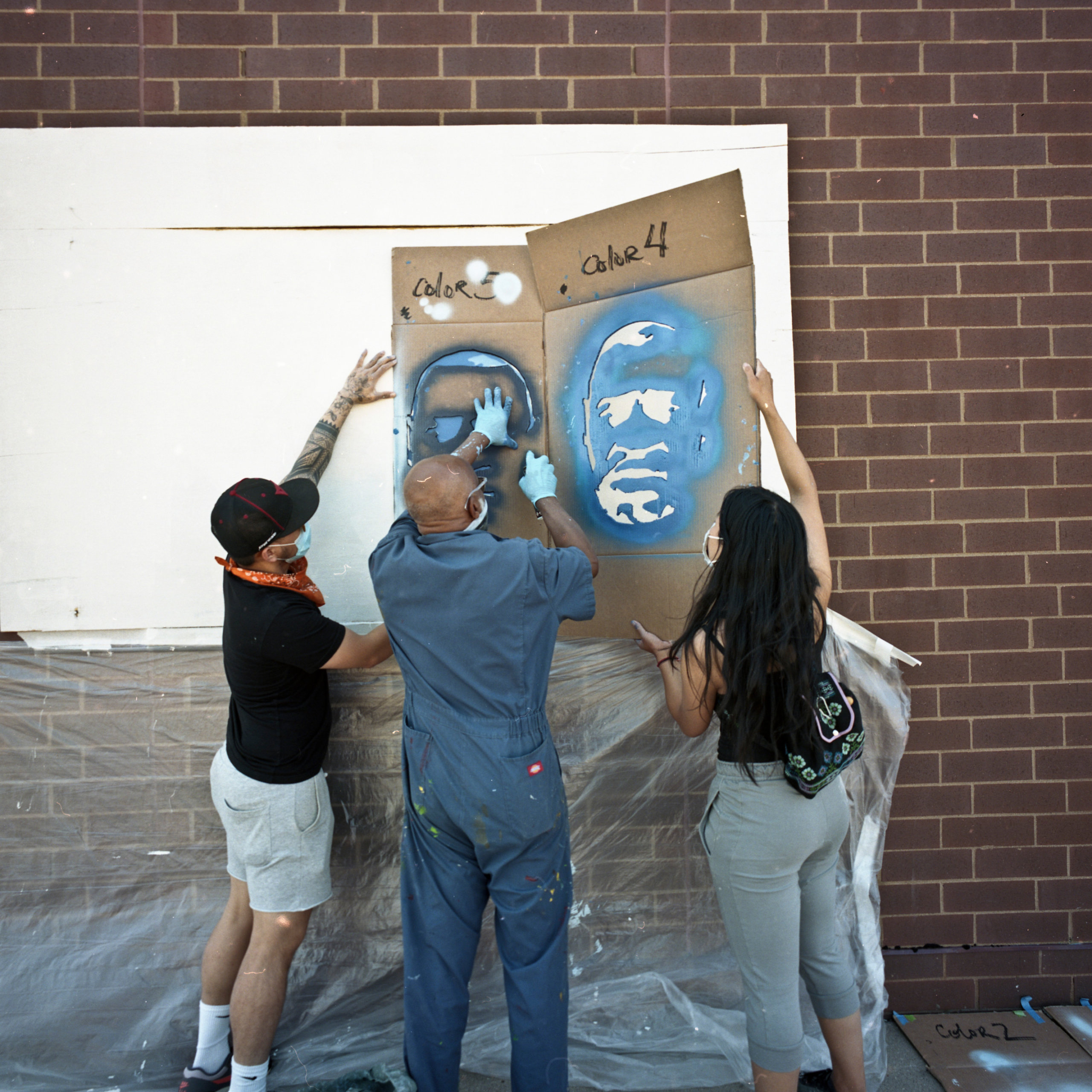 Students spraying a stencil onto the wall