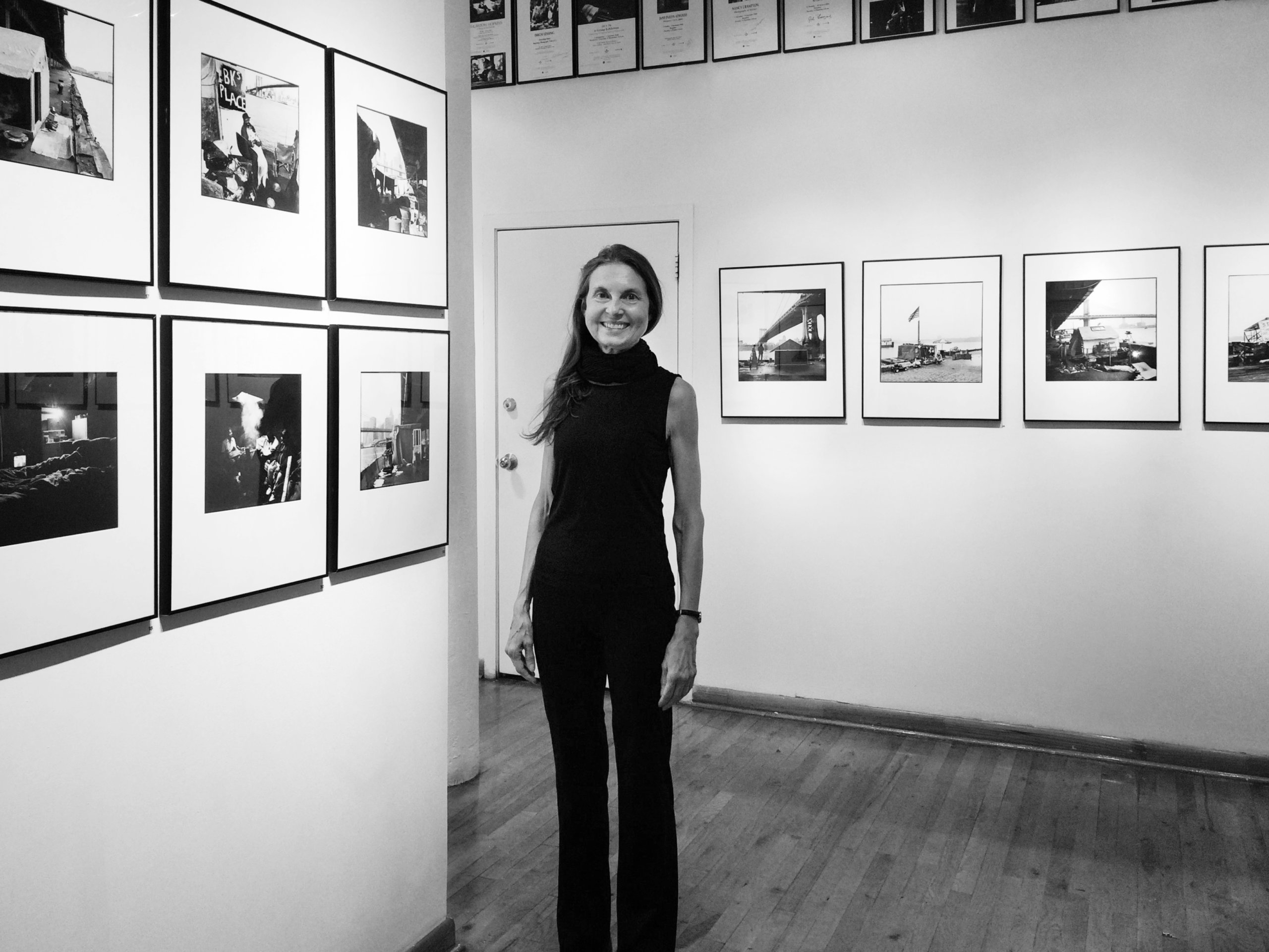 A woman, Margaret Morton, in black and white in a photo gallery