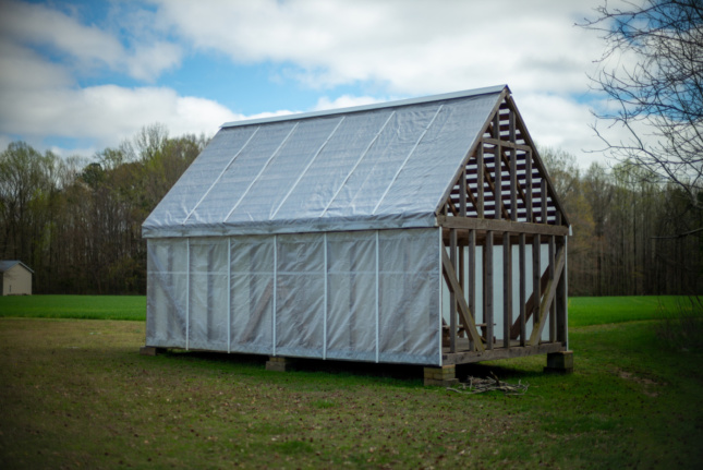 A historically-framed timber shed with clear plastic siding