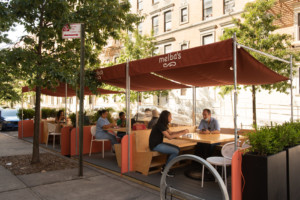 An outdoor dining seating area with Melbas on the canopy