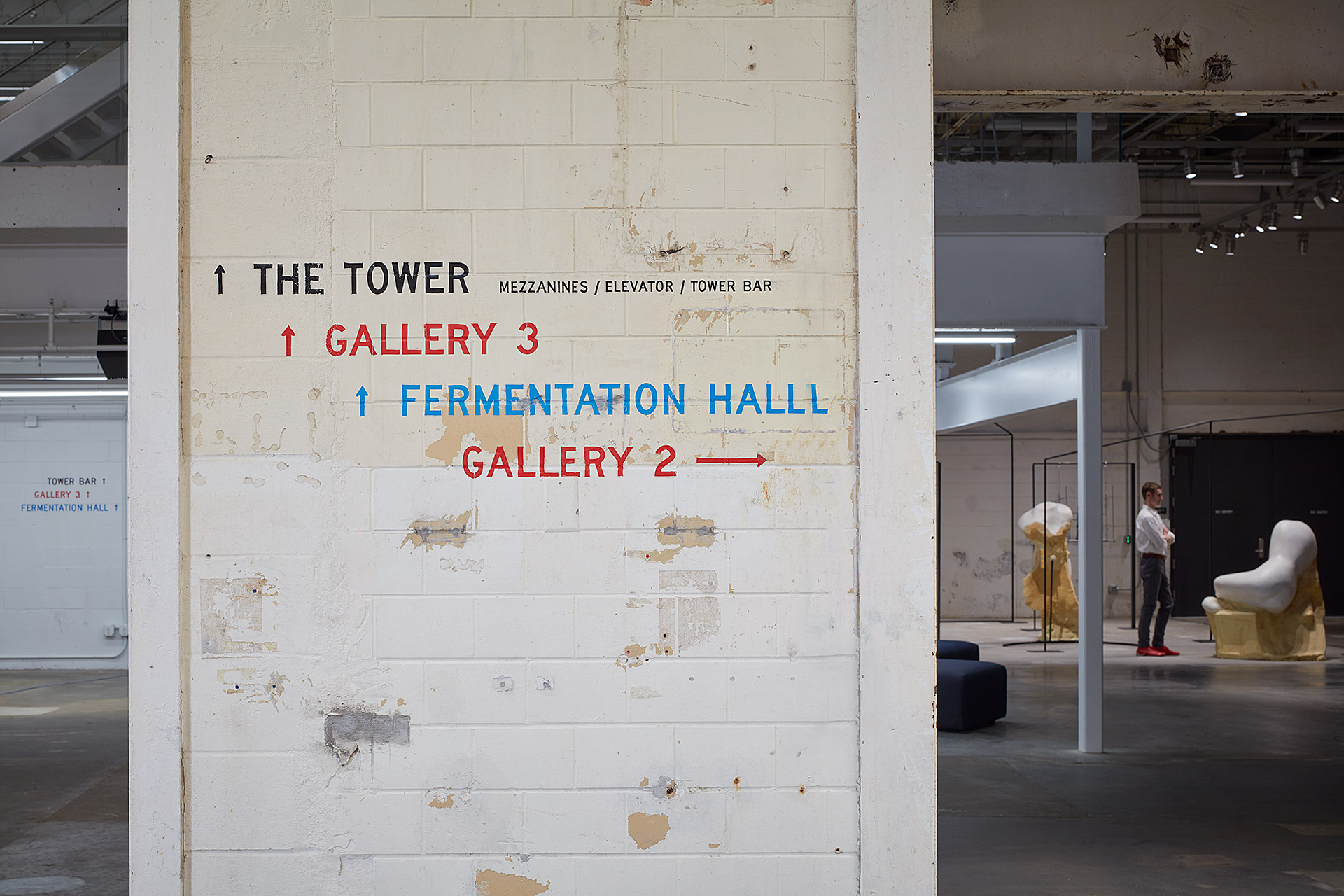A sign on a brick wall leading to the tower, gallery 3, or the fermentation hall