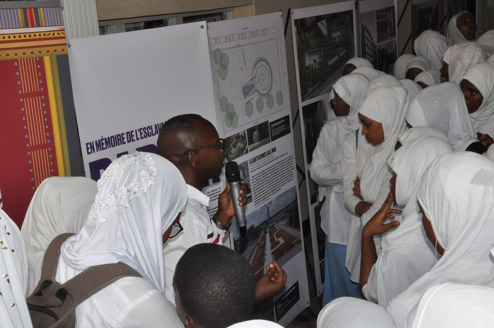 African citizens in white garb around poster boards