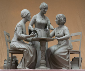 Photo of statue of two women sitting at a table and a third standing behind a table