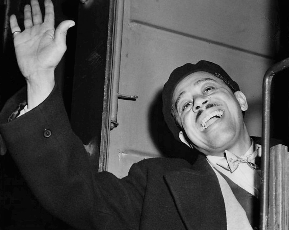 Black and white photo of cab calloway, a man with a mustache waving