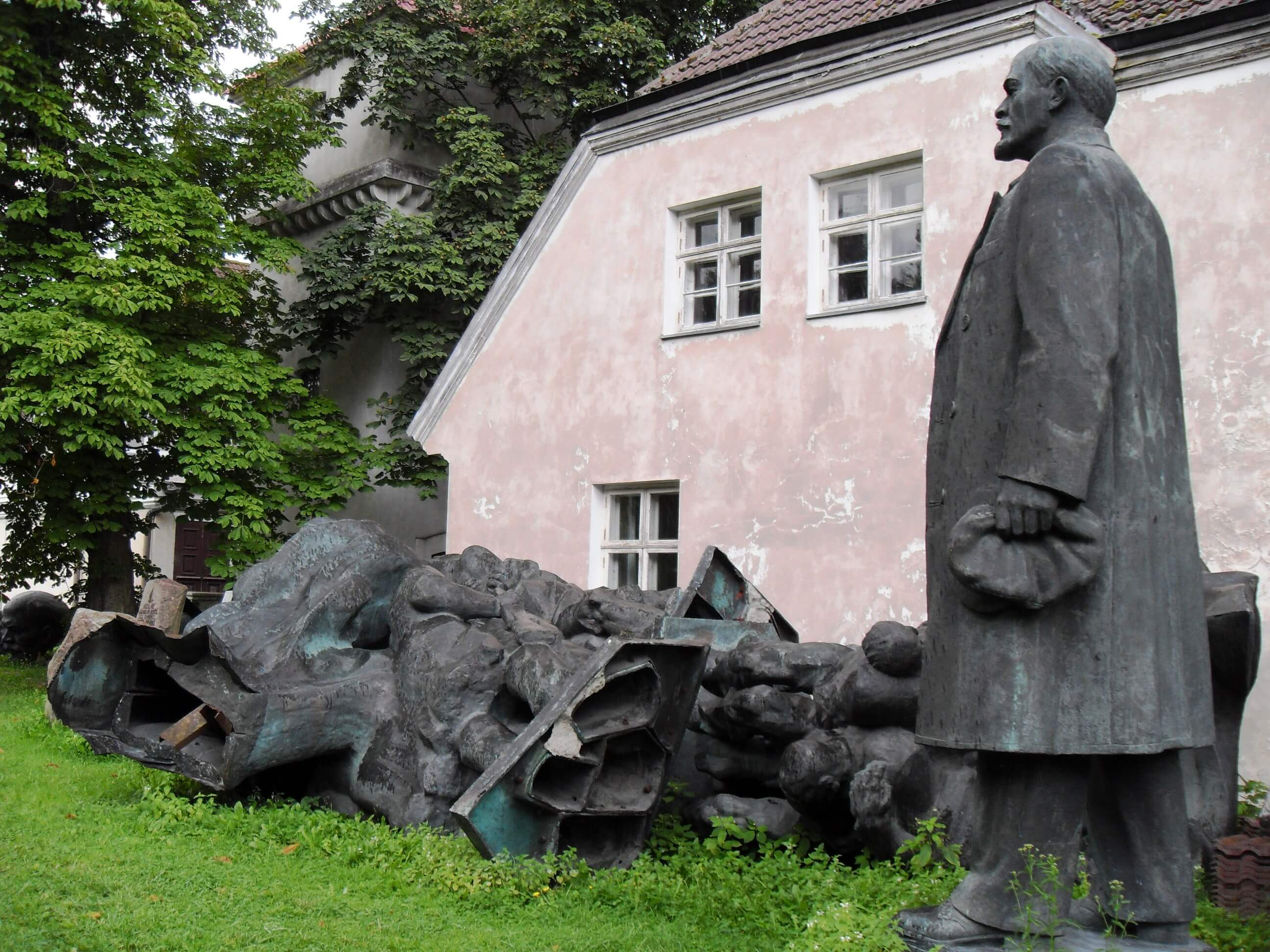 A statue of lenin amid toppled monuments