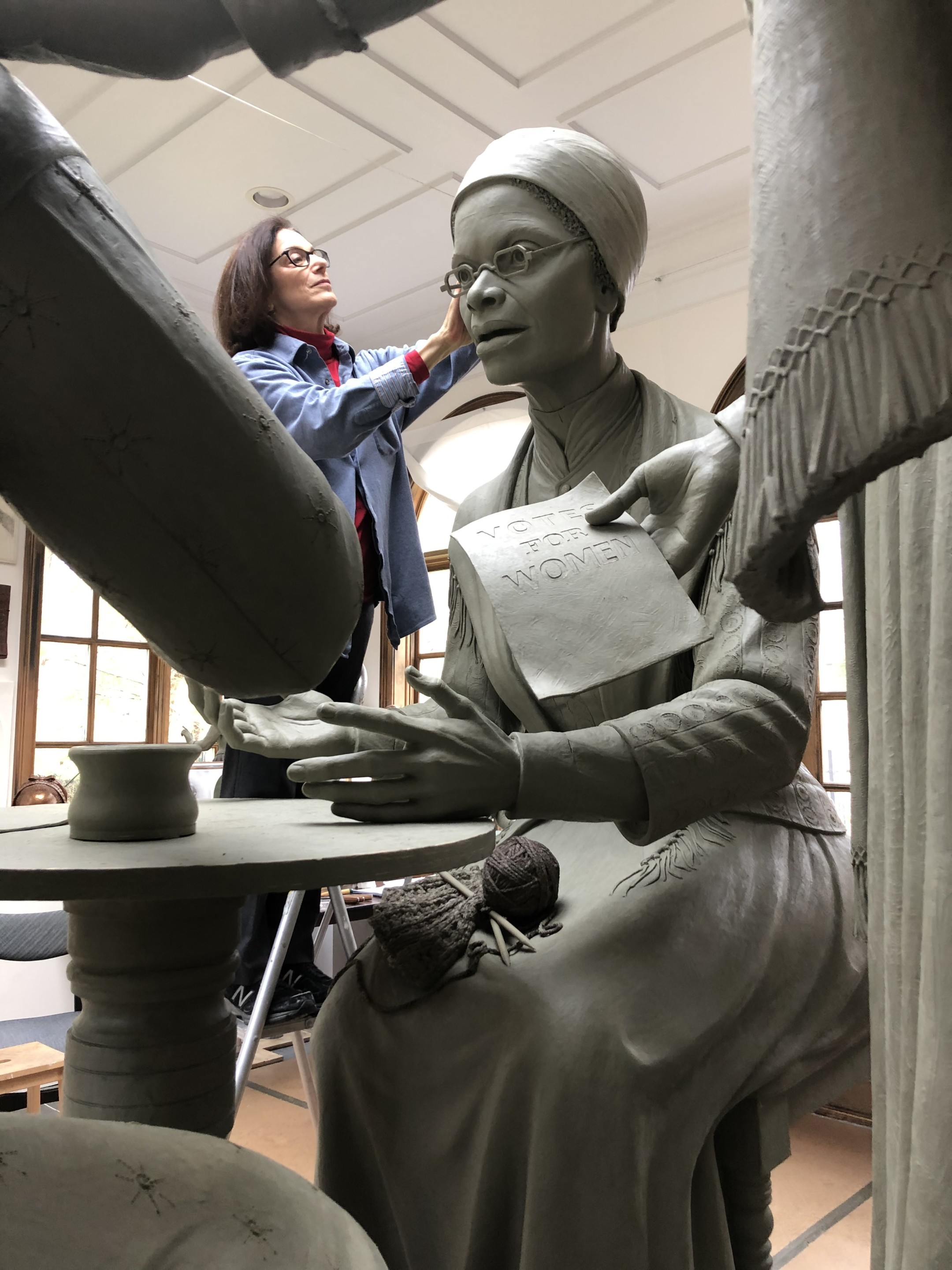 Photo of a sculptor working on a larger than life clay model