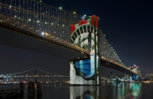 Brooklyn bridge lit up at night with the statue of liberty projected across