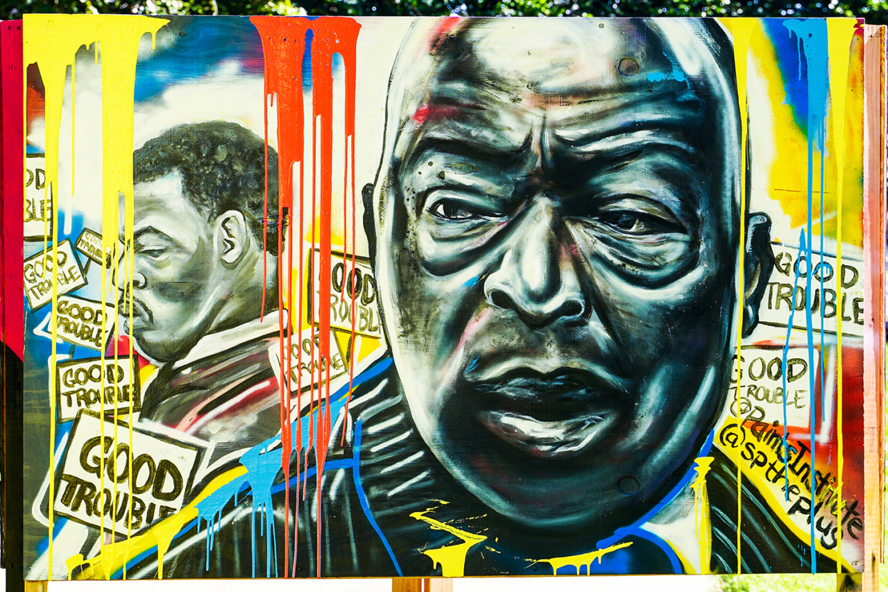 Photo of multicolored mural with John Lewis's face shown from two different ages in his life at murals that matter