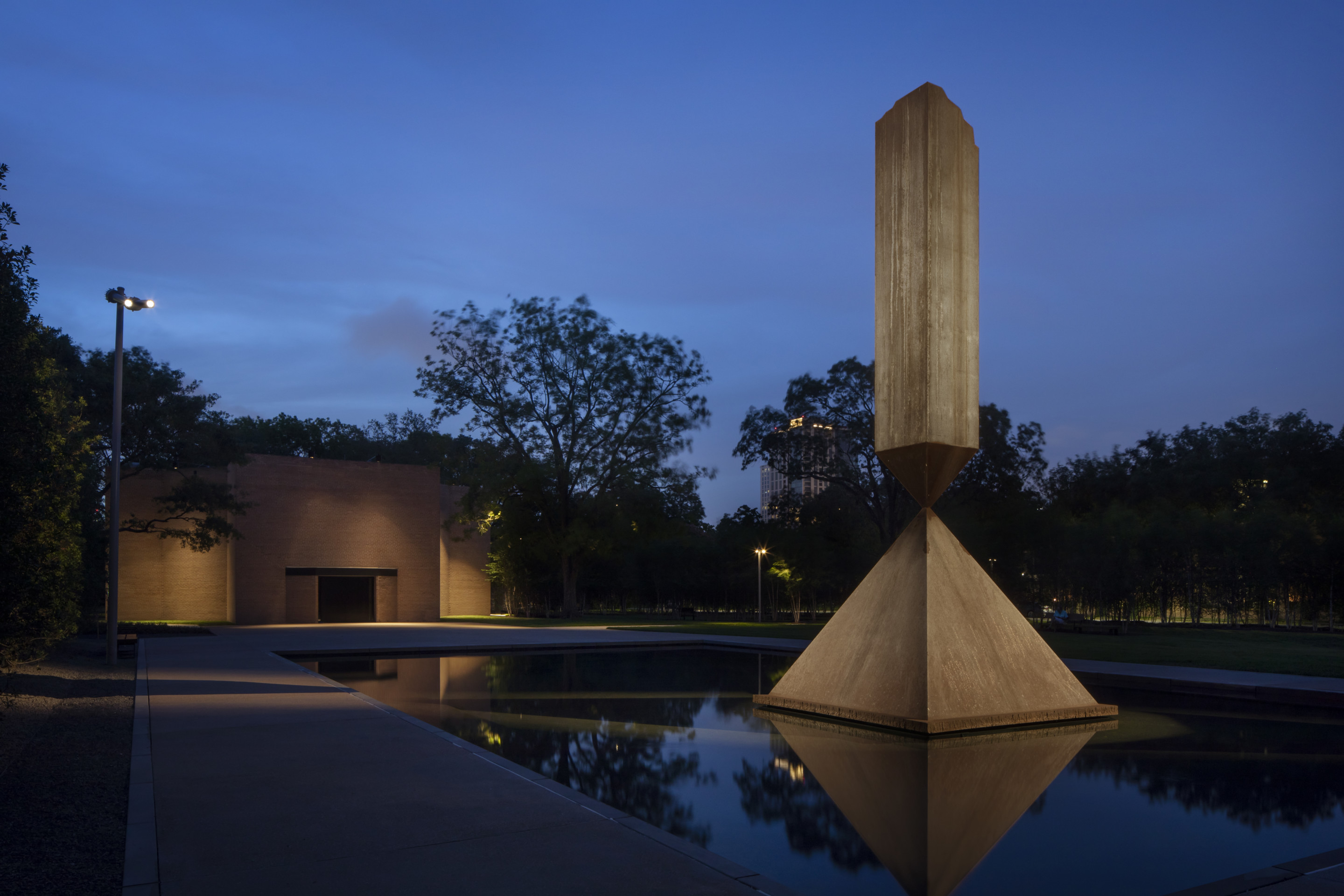 Outside of a squat building at night with an obelisk in foreground