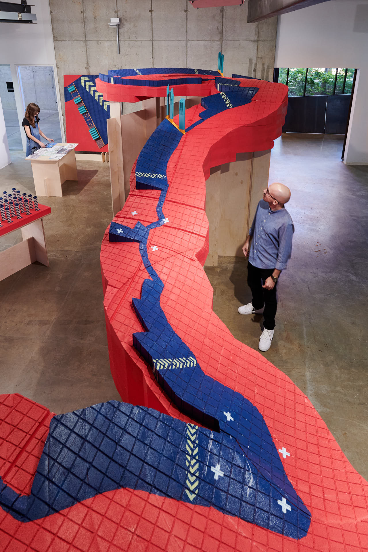 A long red and blue river installation with a man next to it