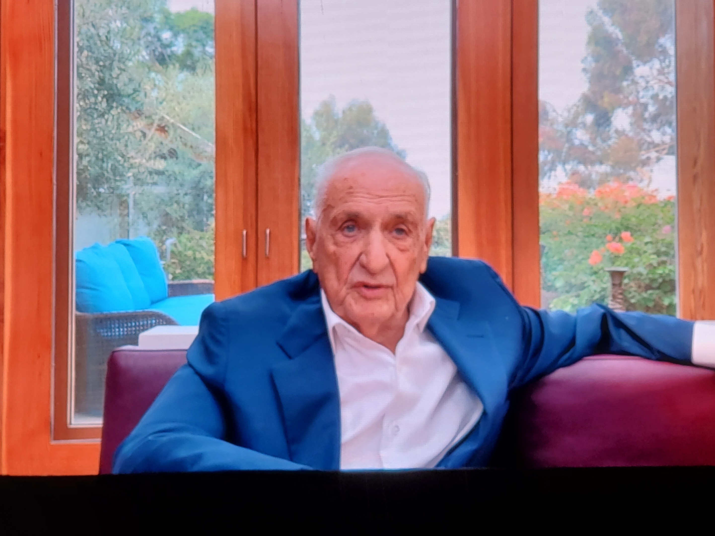 Frank Gehry, an elderly man, delivering comments on a video screen