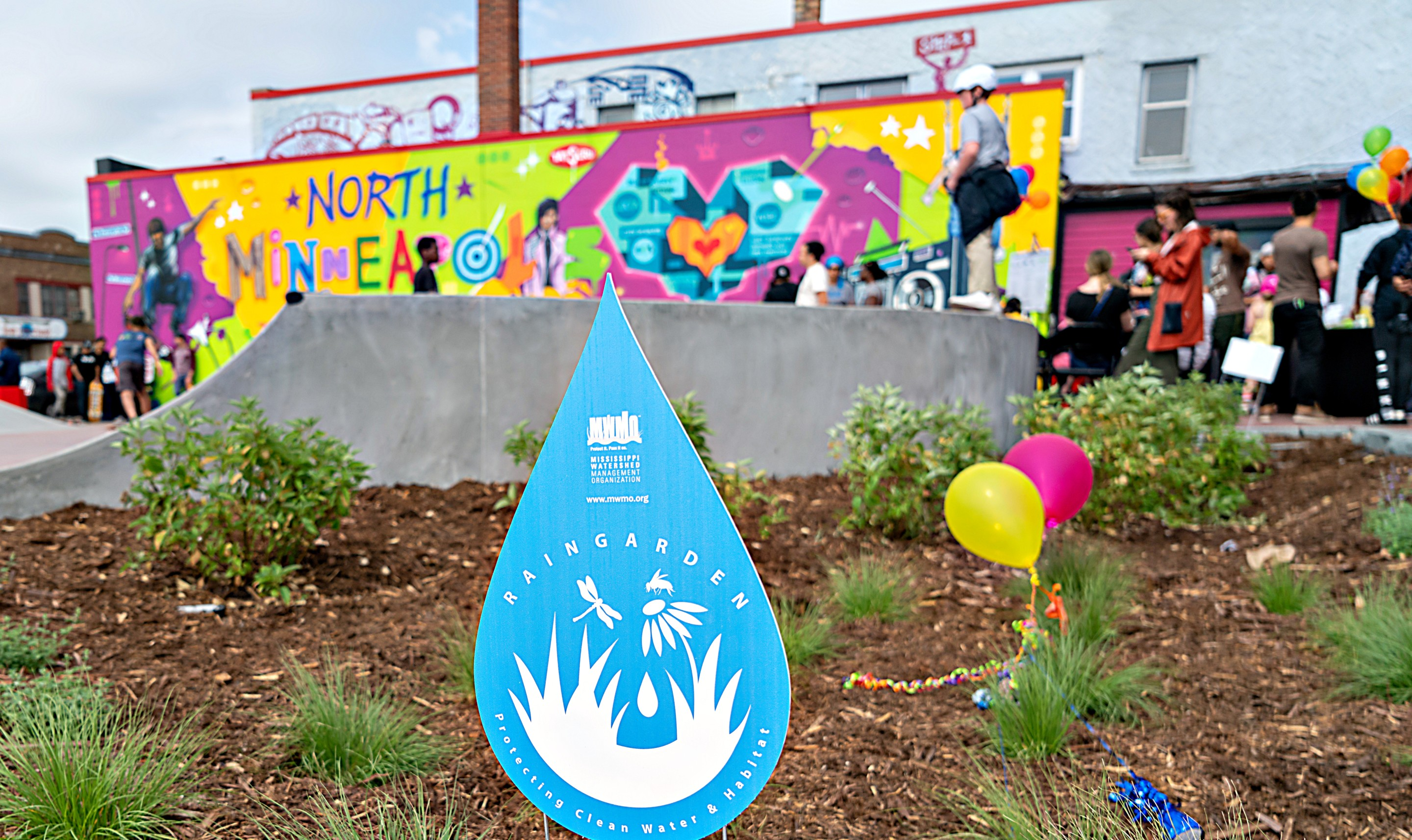 A giant mural in front of a rain garden