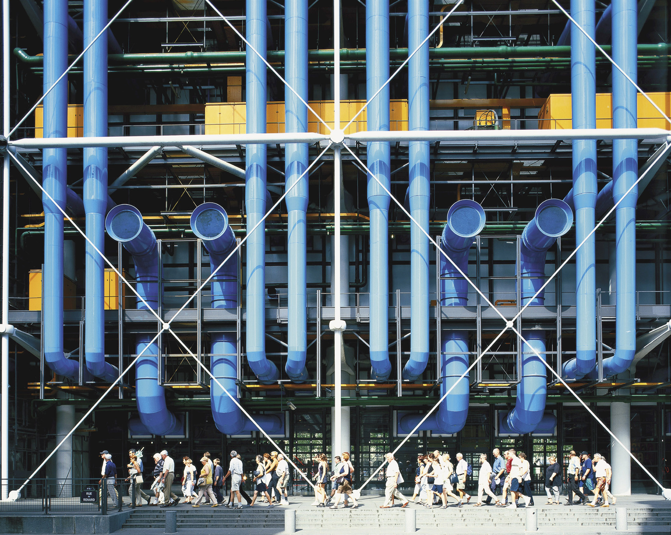 a facade of a contemporary art museum with large blue pipes, designed by Richard Rogers