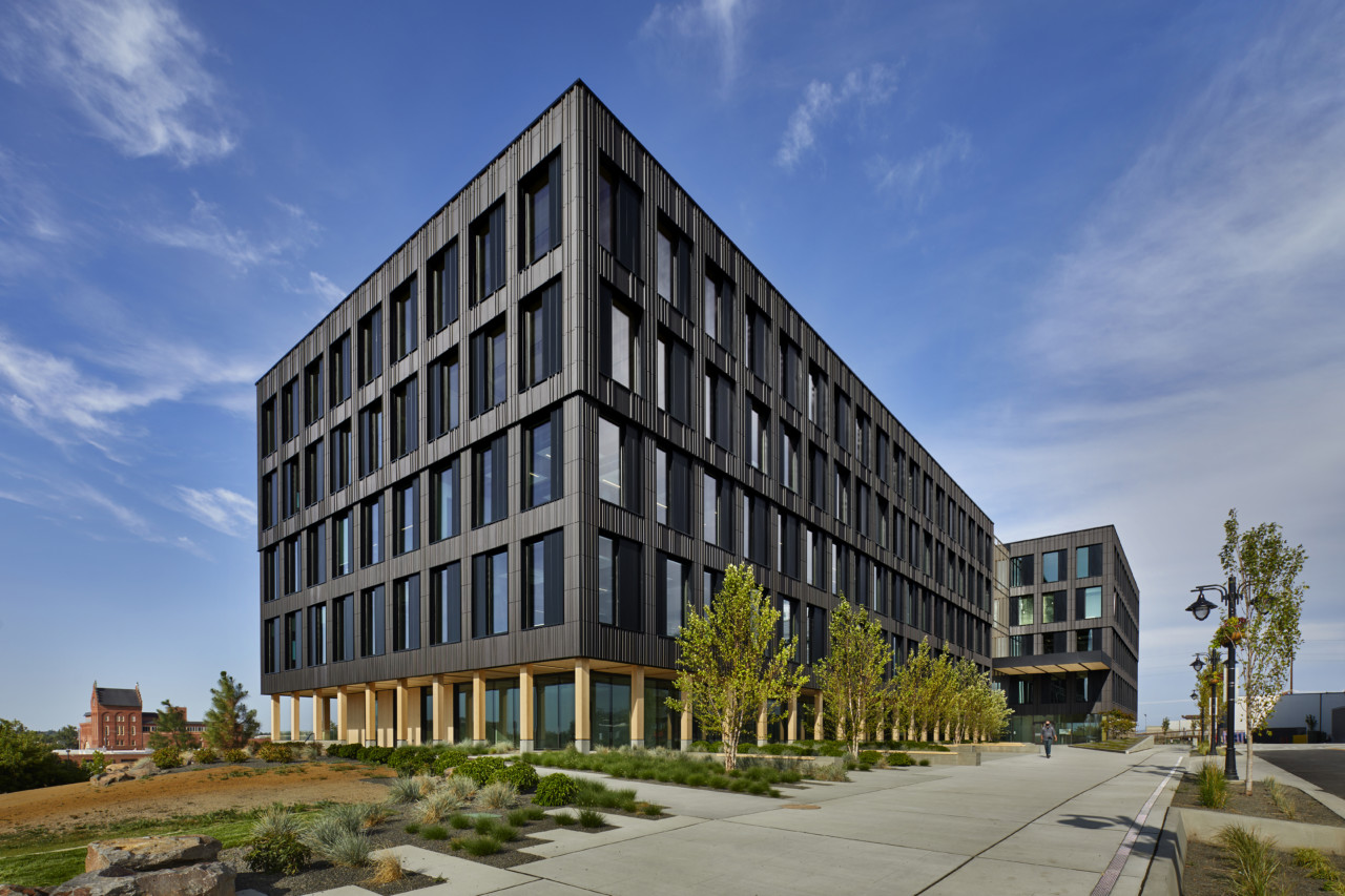Photo of a dark five story building with a rectilinear massing