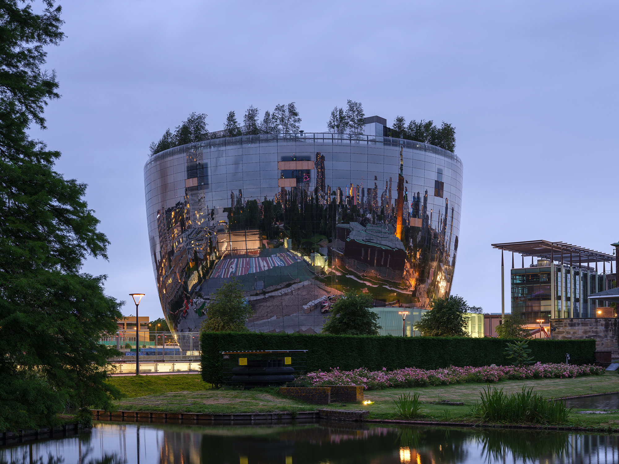 a mirrored, bowl-shaped building in the netherlands at night,, actually an art depot