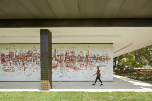 a person walks in front of a large, colorful mural at the SMUD headquarters