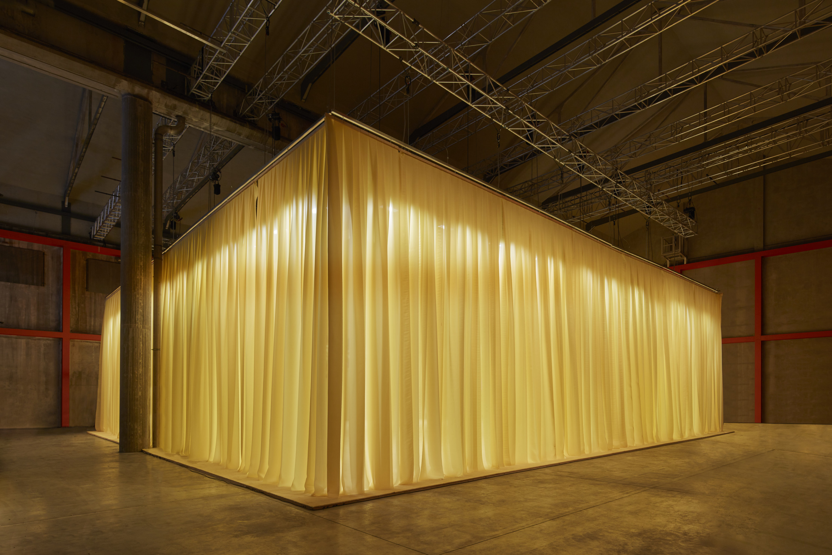 A yellow curtained area inside of a concrete arts space
