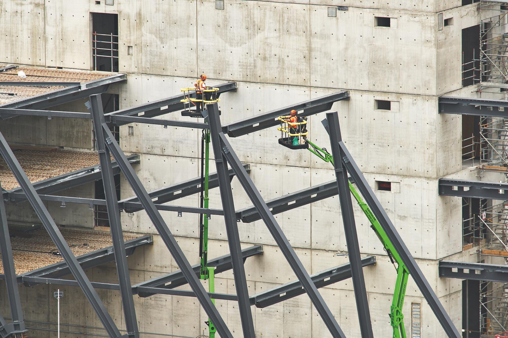 Construction image of beam and exoskeleton installation at a blank concrete wall
