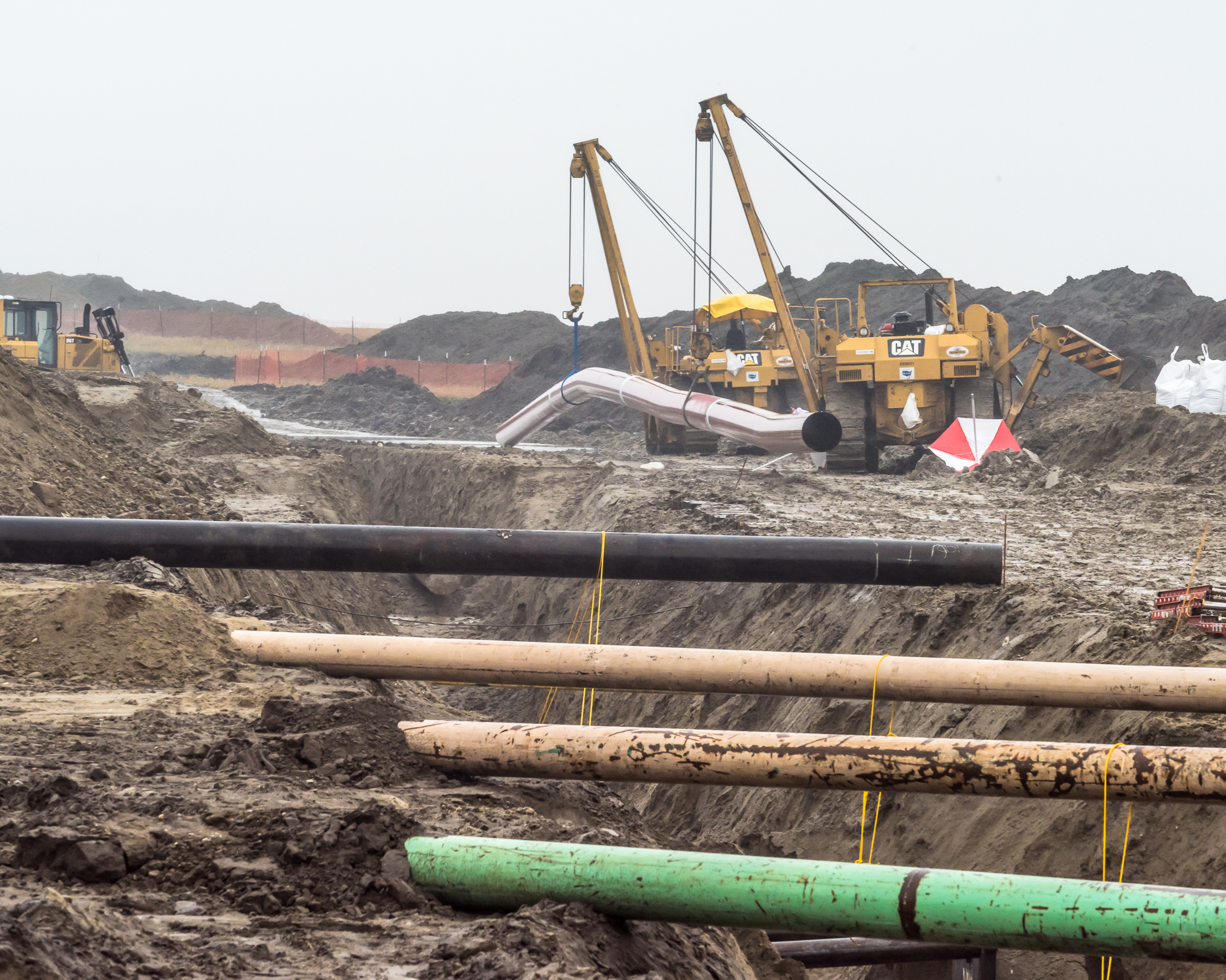 Oil rigs in a field with uncovered pipes, part of a green new deal studio