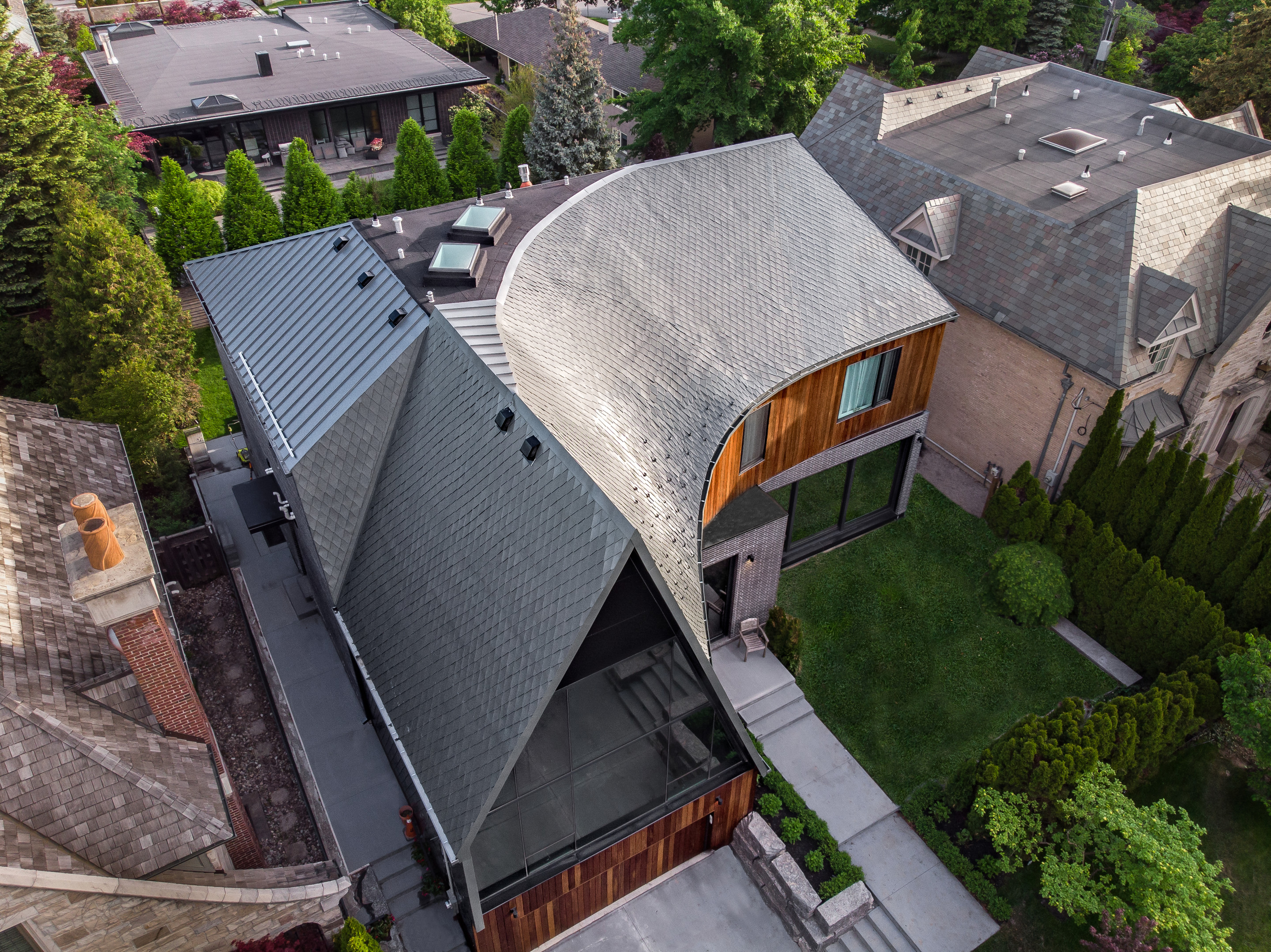 a home from above with a twisting, curving zinc roof
