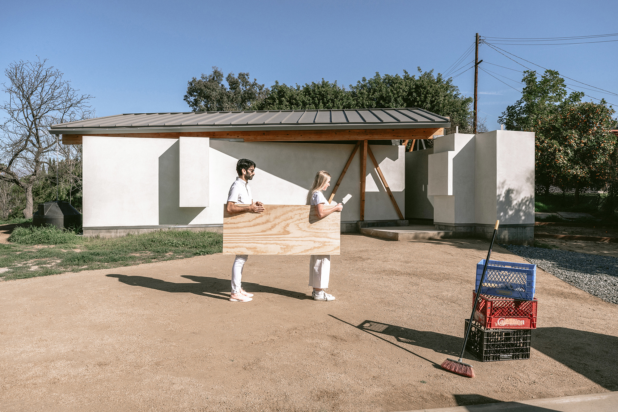 two people in white carrying plywood