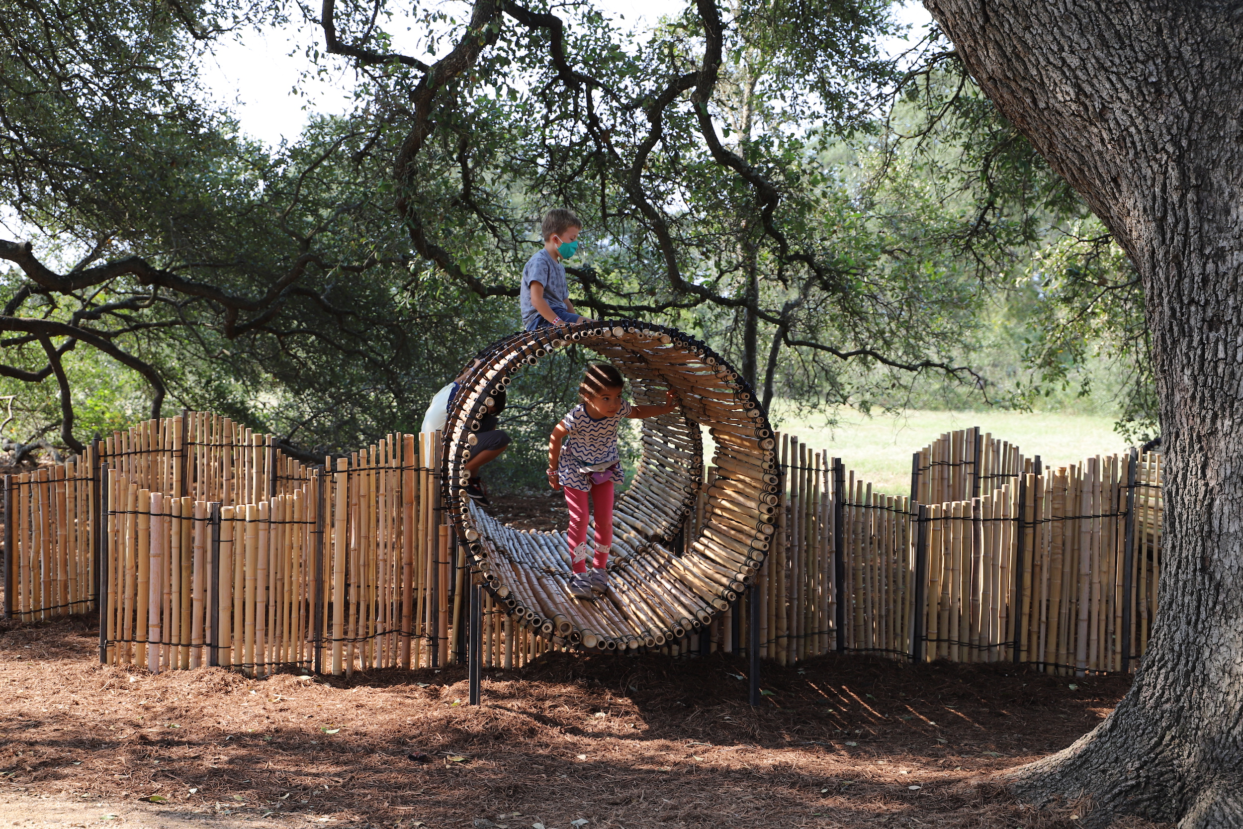 children and parents playing in a play structure