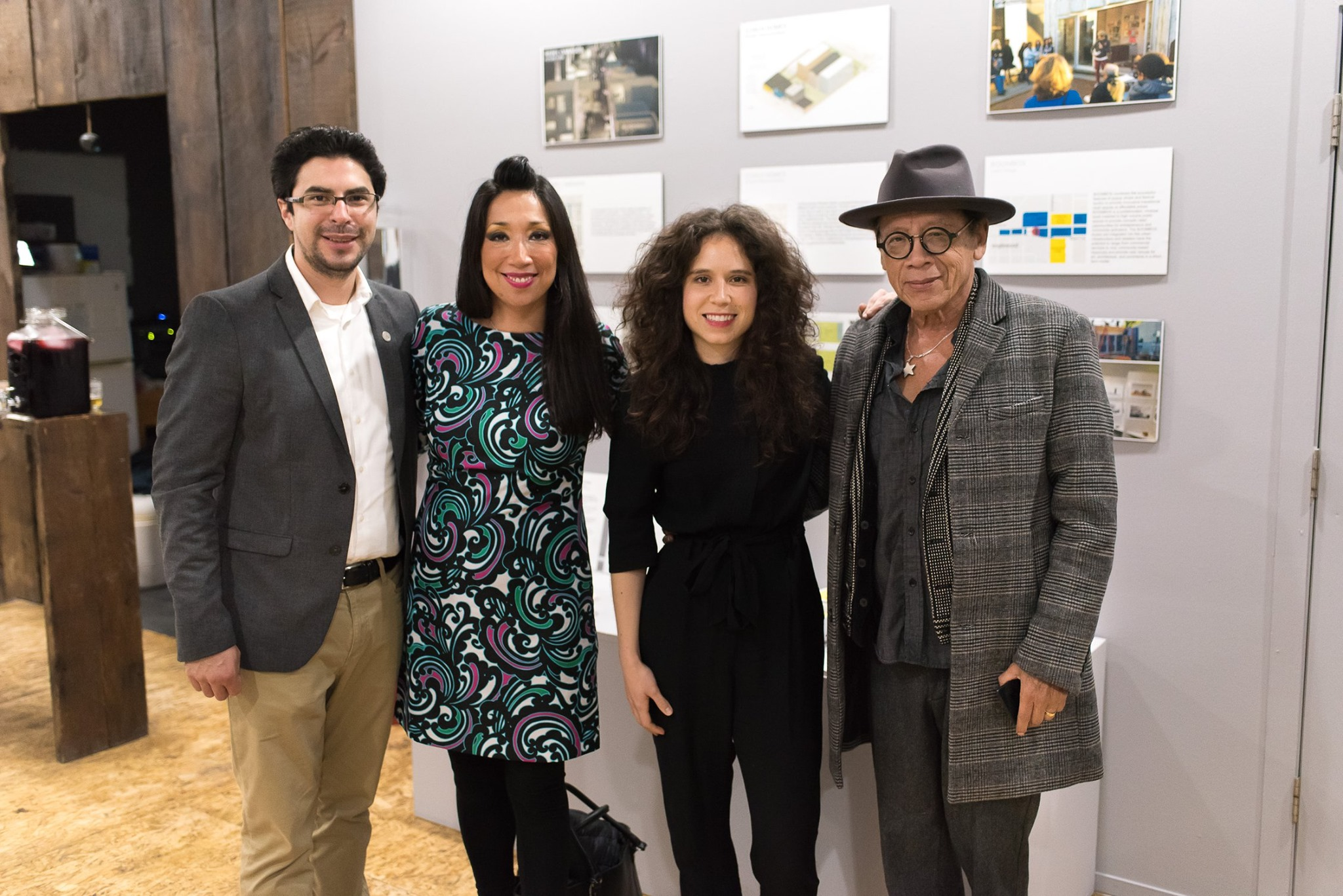 Photo of four people standing in a gallery with diagrams on the walls