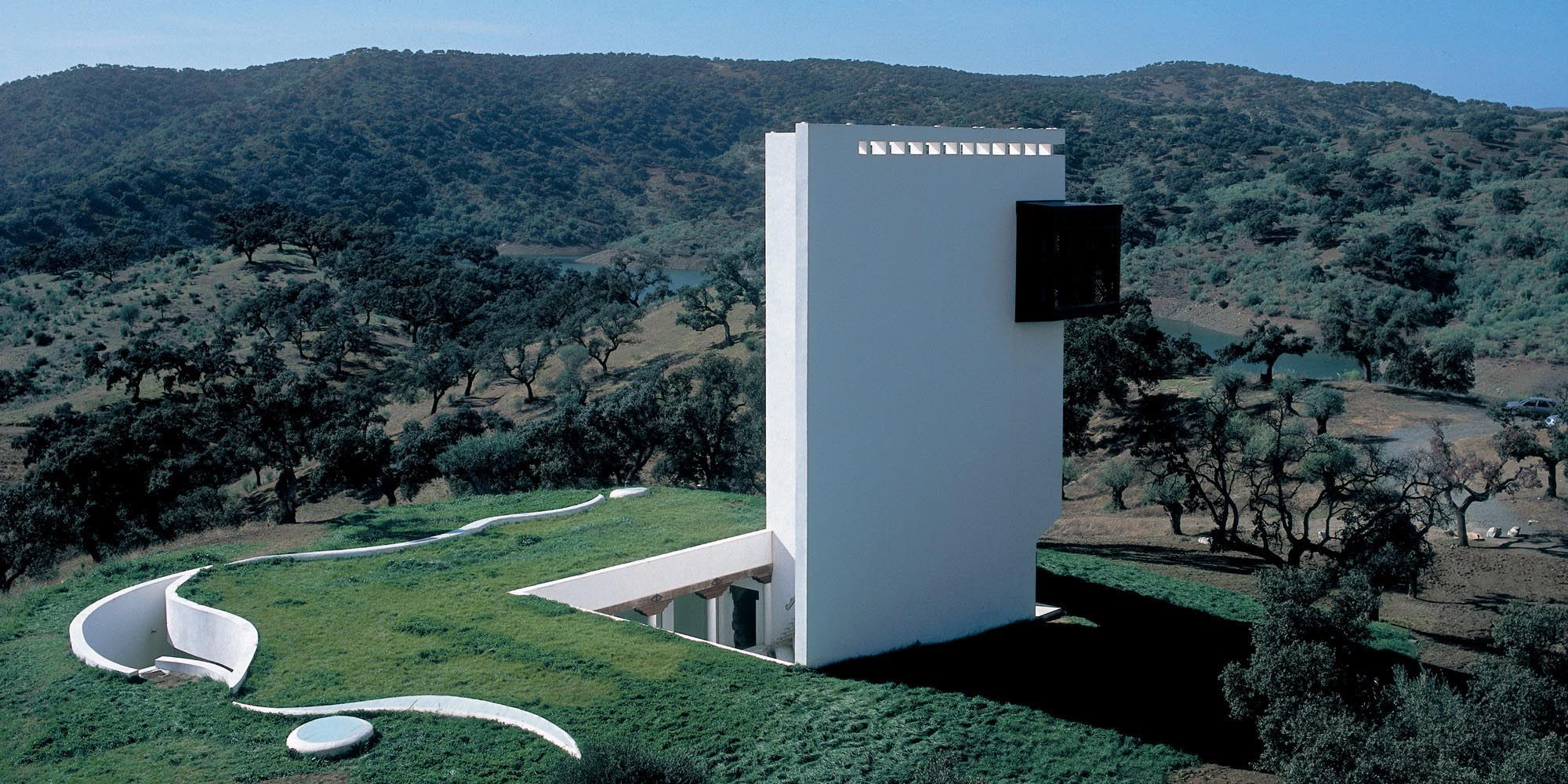 a square whitebuilding integrated into the surrounding landscape