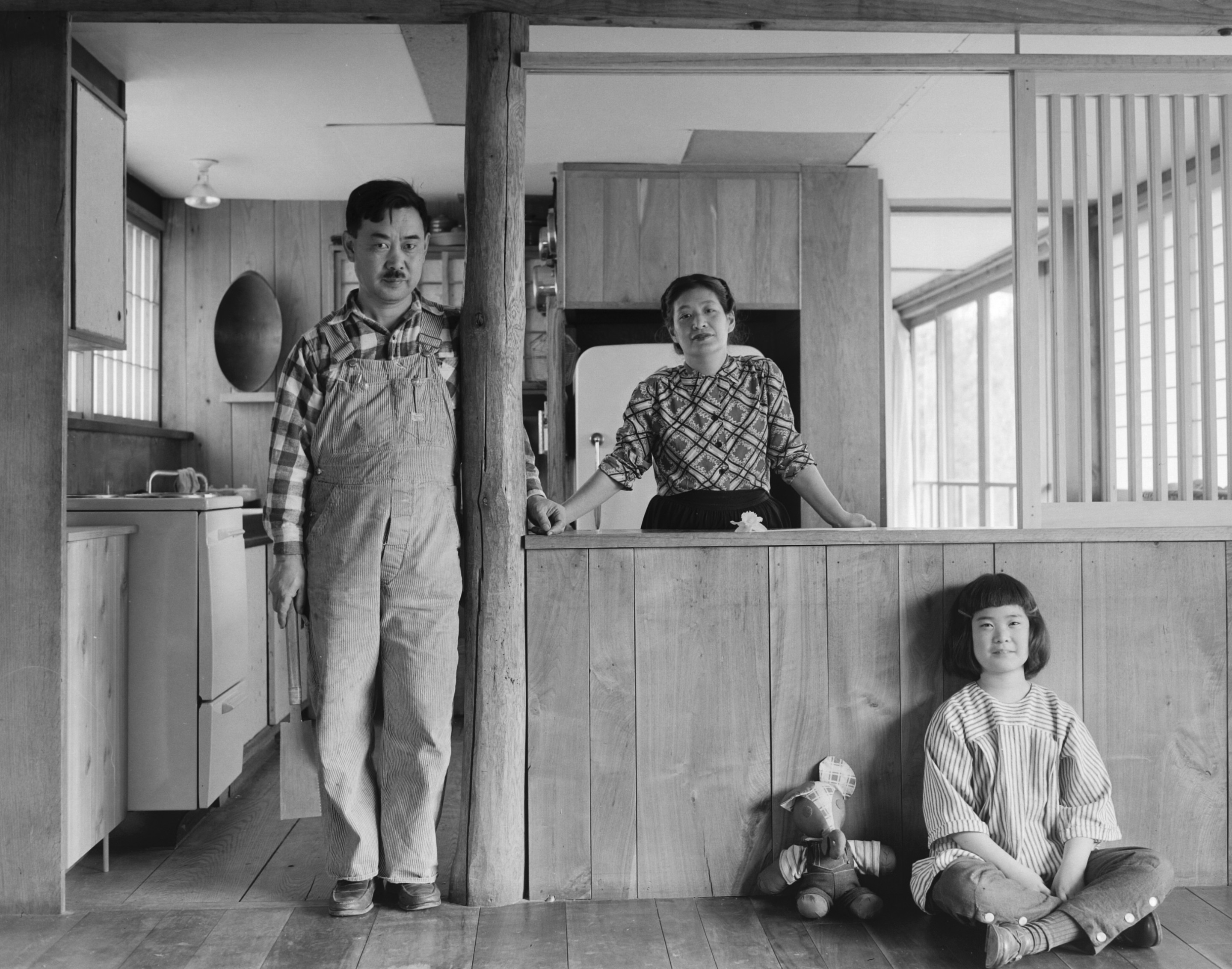 Black and white photo of a man, woman, and child in wood house
