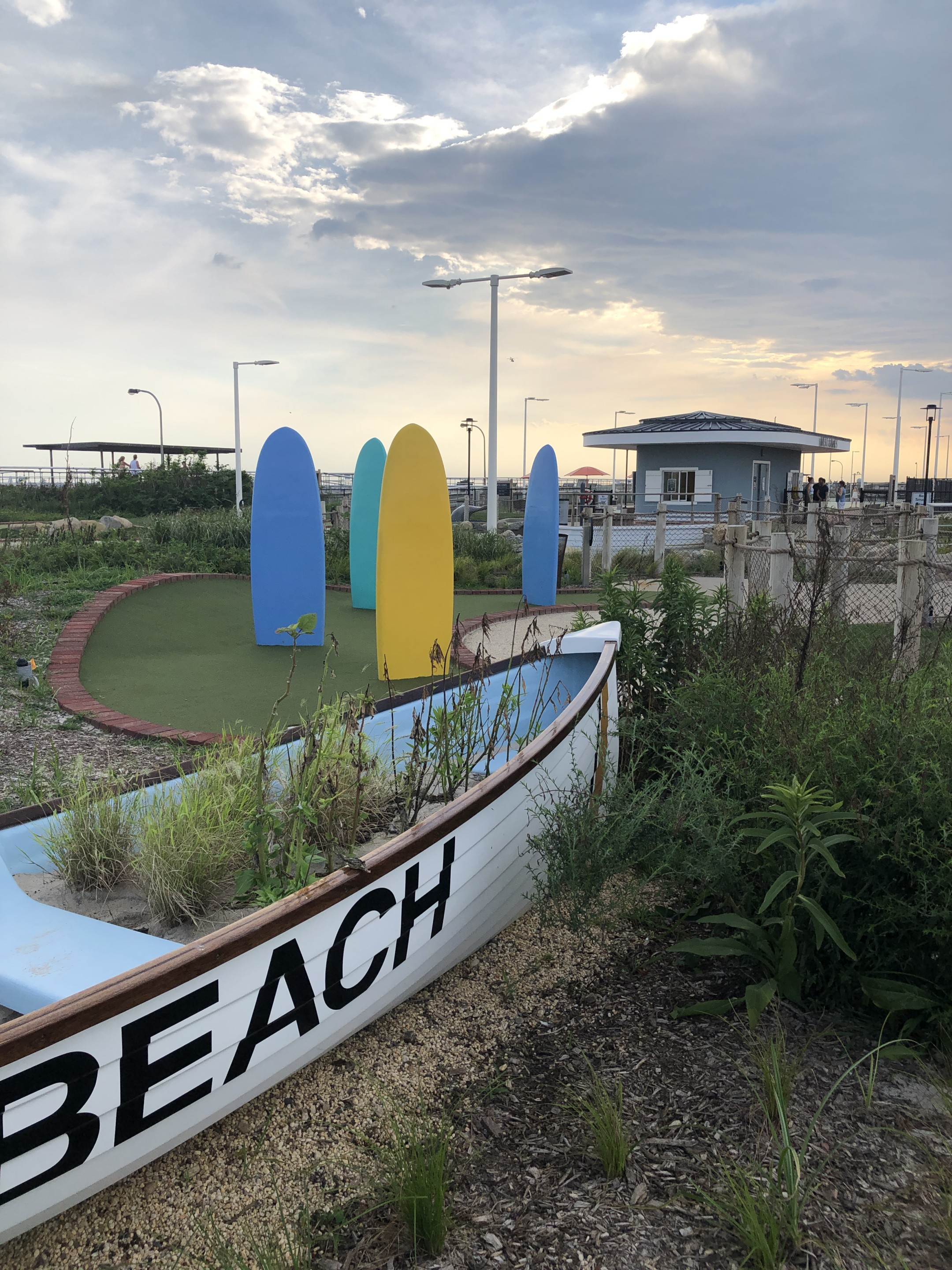 Yellow and blue boards sticking out of mini-golf dunes