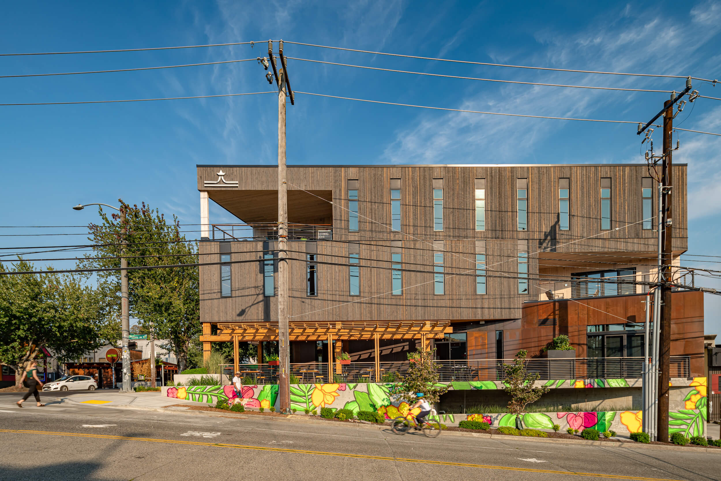 a modern cedar-clad building with a colorful mural