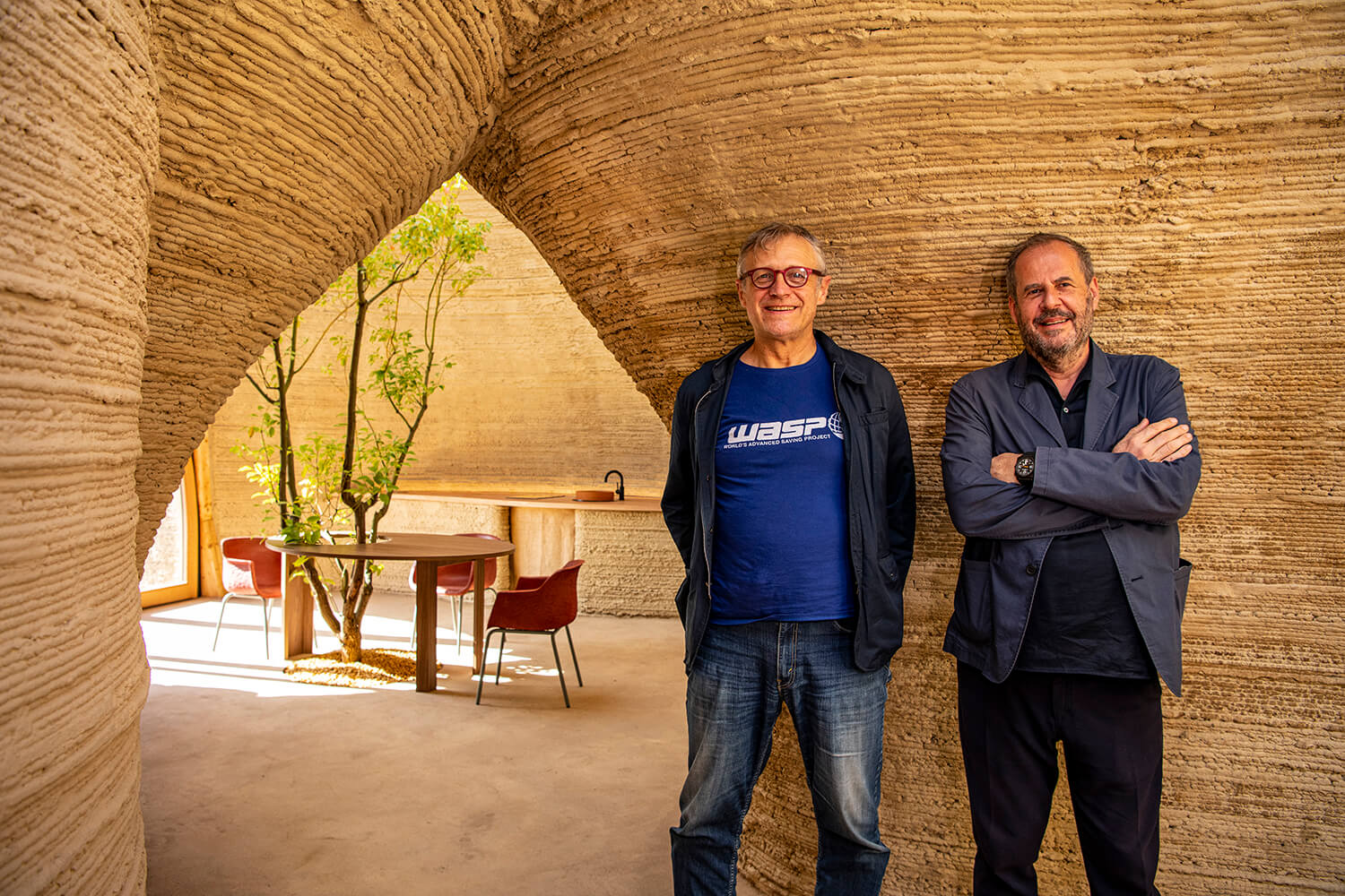two men smile for a portrait inside an innovative clay home