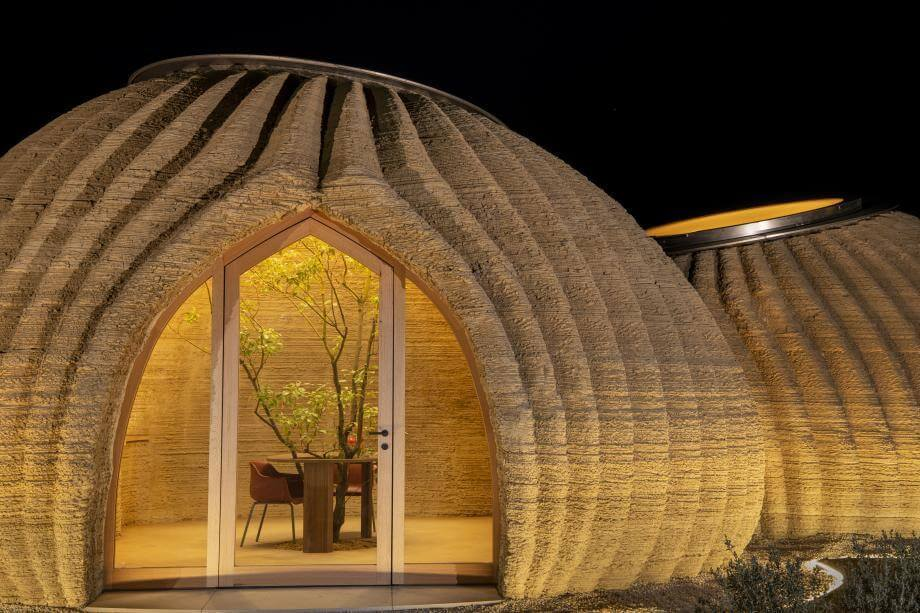 circular-twin clay home pictured at night