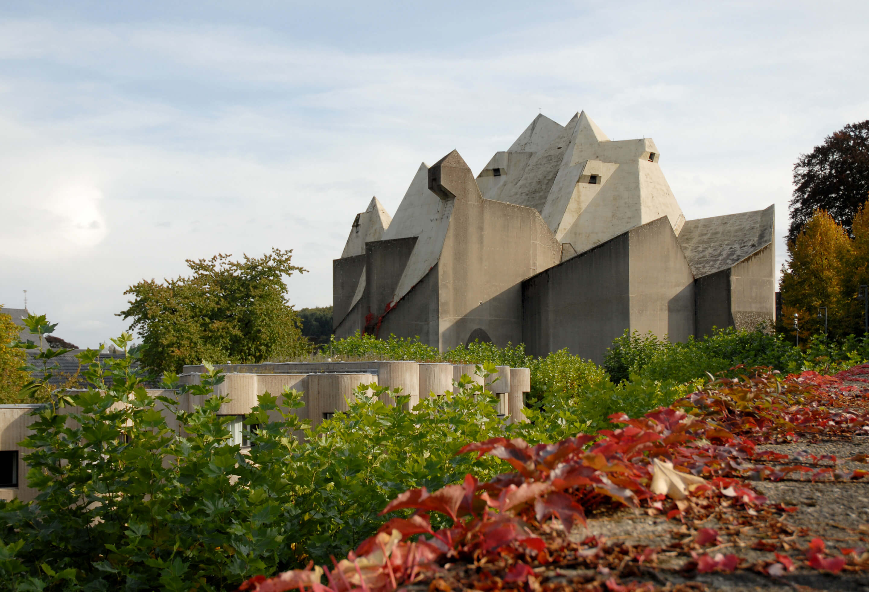 view of an angular concrete church with flowers in the foreground